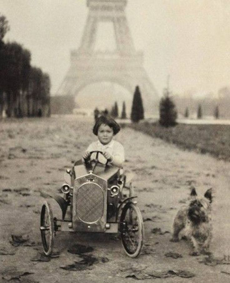 Little Gloria Vanderbilt in a fabulous toy car with her dog running beside, Paris, ca. 1920s